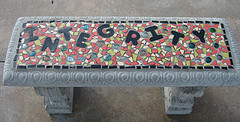"Stone bench with the word ""integrity"" embedded into a mosaic"