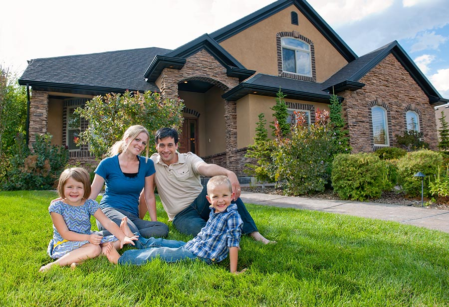 Smiling family on front lawn of a house