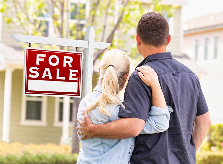 Caucasian Couple Facing Front of Sold Real Estate Sign and House