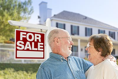 Older couple in front of home for-sale sign