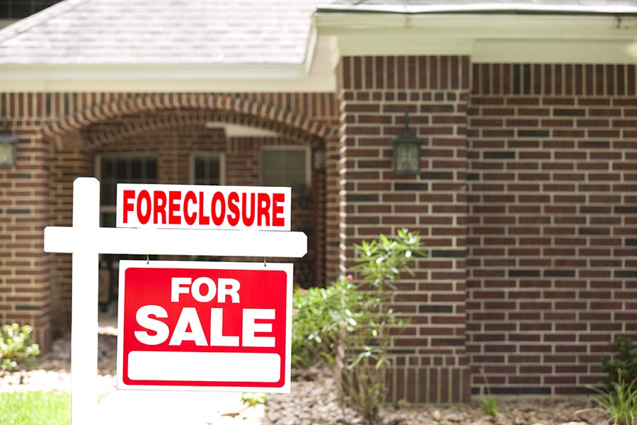 House for sale, foreclosure sign in front yard. No people.
