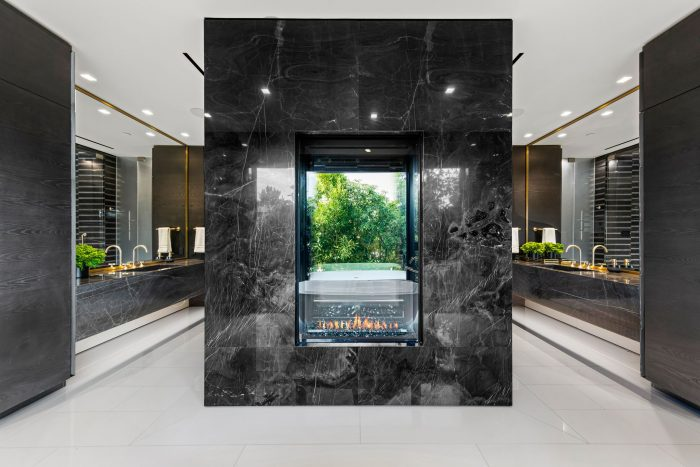 An elegant primary suite features a black-marble encased shower with fireplace.