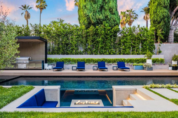 The oversized backyard boasts a sparkling pool with a see-through glass wall.