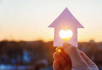 A hand holding a paper house with a heart cut in it