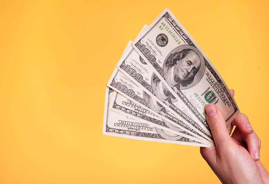 A hand holding five $100 bills