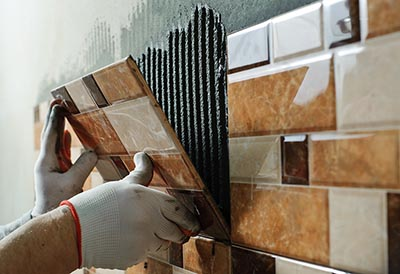 Tiler placing ceramic wall tile in position over adhesive