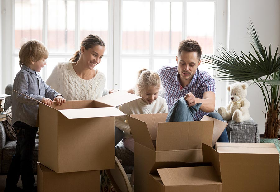 Young happy family with children packing boxes on moving day