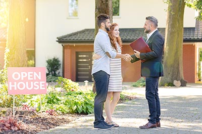Real estate professional welcoming visitors to an open house