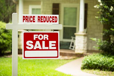 A home for-sale sign with a price reduction