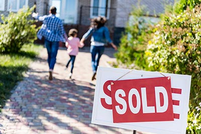 Family walking into house behind sold sign