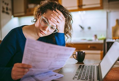 Stressed-out young woman looking at paperwork.