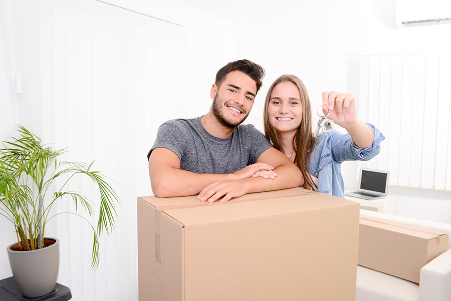 cheerful and happy young couple holding the keys of their new home with moving cardbox during move into new apartment