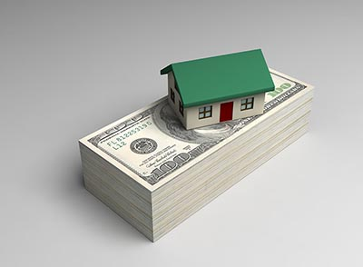House sitting on a stack of money