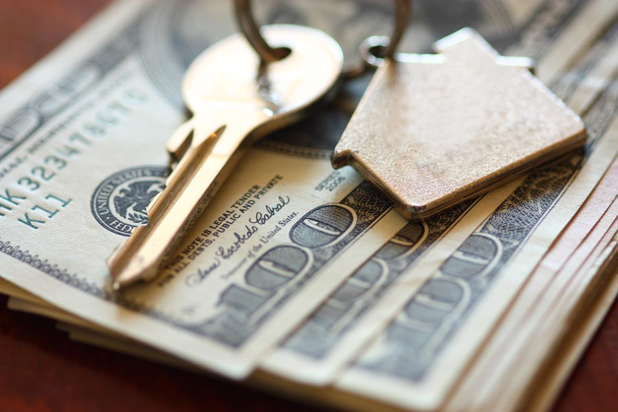 Set of house keys laying on hundred dollar bills