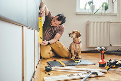 Man remodeling a home with his dog