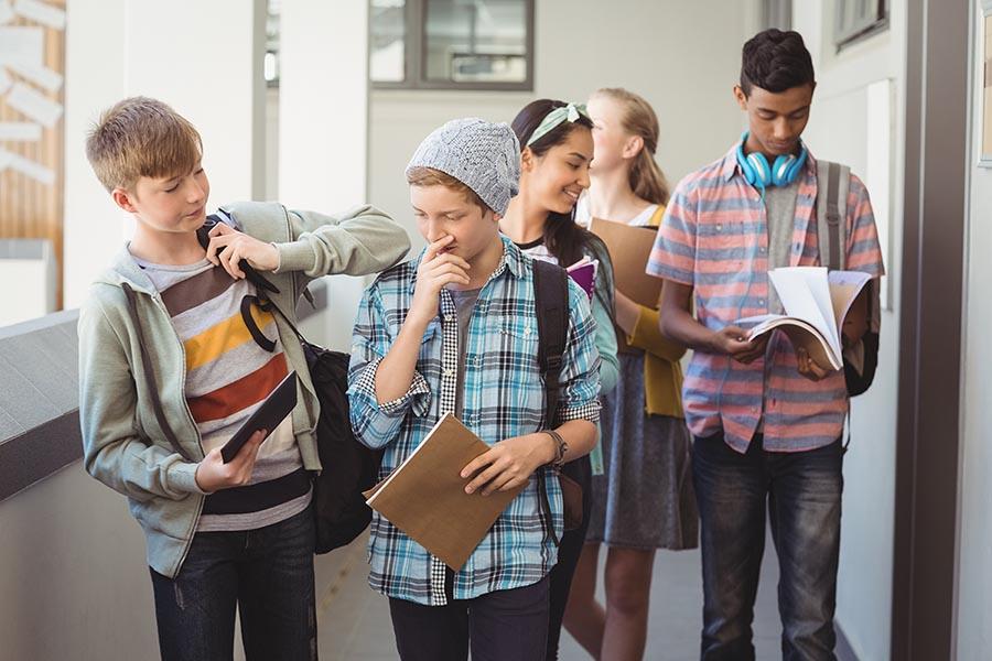 Group of classmate walking in corridor at school