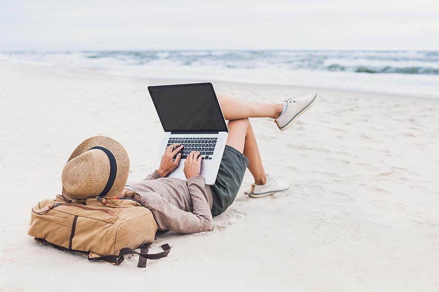 Young woman using laptop on a beach