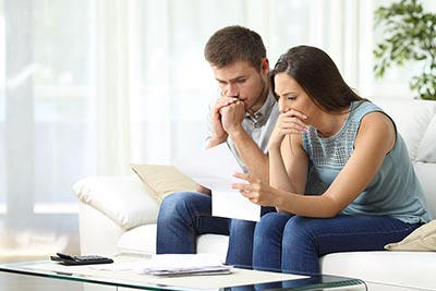 Worried couple examining papers